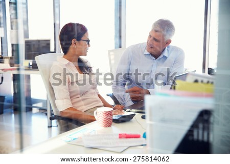 Office colleagues talking at work - stock photo