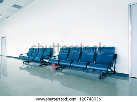 Office corridor with blue chairs and white wall - stock photo