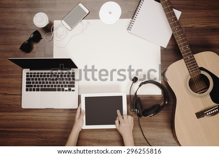 Office desk background, Hand touchscreen on tablet PC with acoustic guitar, headphones recording scene project ideas concept. mobile phones, laptop computer, View from above with copy space - stock photo
