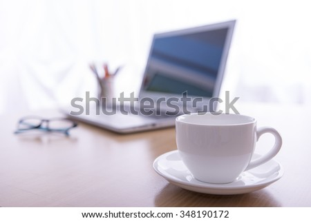 Office desk selective focus on white coffee cup