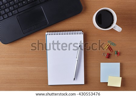 Office Desk Table with a Blank Notebook, Cup of coffee, Pen, Piece of Paper and Supplies. Workplace Top View on a Wooden Background with Copy space for text or Image - stock photo