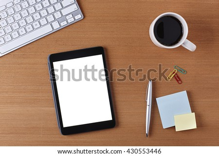 Office Desk Table with a Blank Tablet, keyboard, cup of coffee, pen, blank piece of paper and supplies. Workplace Top View on a Wooden Background with Copy space for text or Image - stock photo