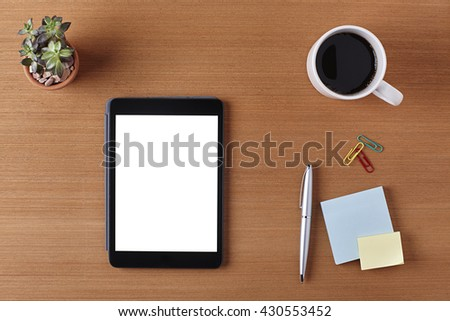 Office Desk Table with a Blank Tablet, Plant Pot, Cup of coffee, pen, blank piece of paper and supplies. Workplace Top View on a Wooden Background with Copy space for text or Image - stock photo