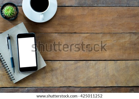 Office desk  table with blank screen smartphone, notebook pen and coffee cup .Top view with copy space - stock photo
