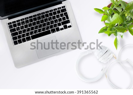Office desk table with computer, headphones and flower. Top view with copy space