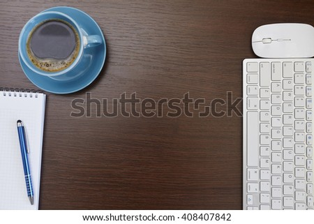 Office desk table with computer, supplies and coffee cup - stock photo