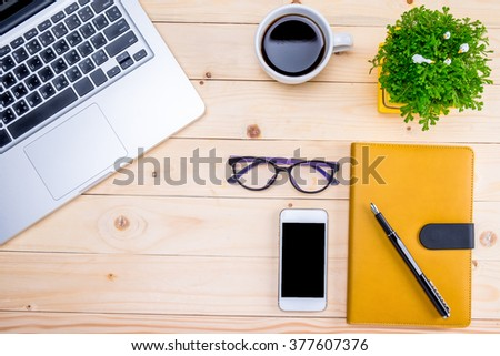 Office desk table with computer, supplies, smartphone, glasses, pen on notebook, cup of coffee and flower. Top view with copy space (selective focus) - stock photo