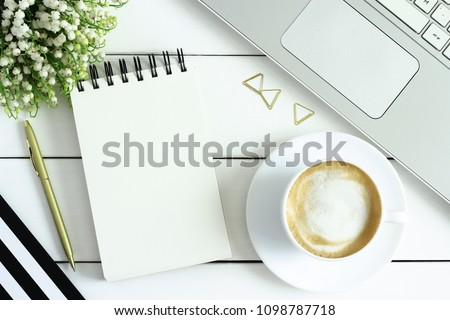 Office desk table with cup of coffee, laptop, notebook and lily of the valley flowers. Coffee break, ideas, notes or plan writing concept. Top view, flat lay. White wooden table, top view.