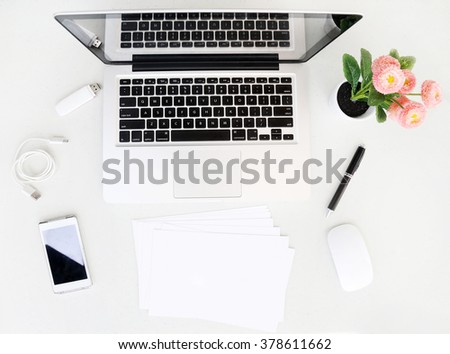 Office desk table with laptop, office supplies and flower pot - stock photo