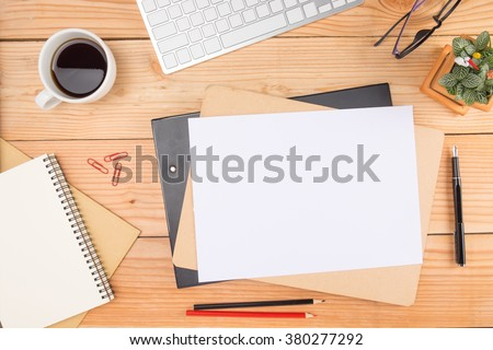 Office desk table with smartphone, pen on notebook, cup of coffee and flower. Top view with copy space (selective focus) - stock photo