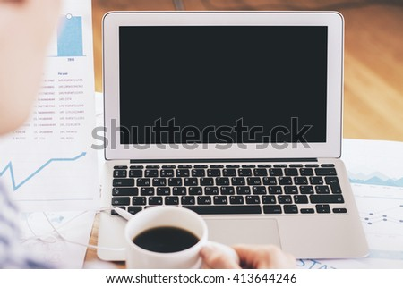 Office desk with blank laptop and businessman looking at report and drinking coffee. Mock up - stock photo