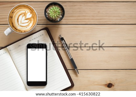 Office desk with blank screen smartphone, pen, notebook and coffee cup on rustic wood table.Top view with copy space - stock photo