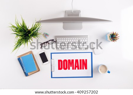 Office desk with DOMAIN paperwork and other objects around, top view - stock photo