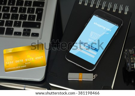 office desk with internet store page on mobile  phone and plastic card