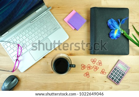 Office desk with modern touch screen pc, diary planner, and morning coffee.