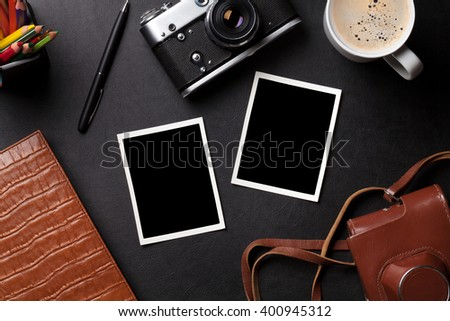 Office desk with photo frames, camera, coffee and notepad. Top view with copy space
