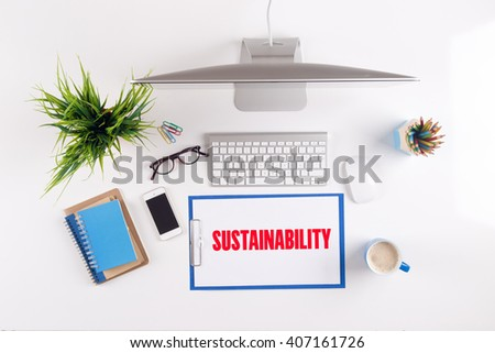 Office desk with SUSTAINABILITY paperwork and other objects around, top view - stock photo