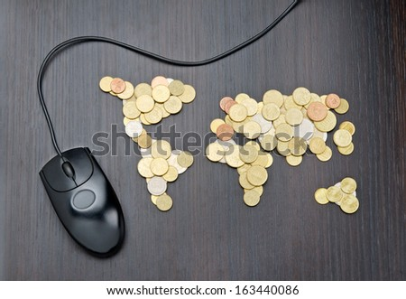 Office desk with world map made of money coins and computer mouse - stock photo