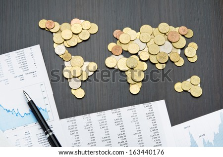 Office desk with world map made of money coins and report sheets - stock photo
