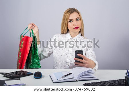 Office, finances, internet, business, success and people concept-Young beautiful  business woman  with colored bags with phone in hand on gray background