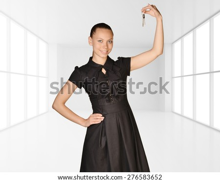 Office girl standing on background of light interior and is holding keys. - stock photo