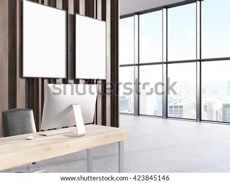 Office interior with computer on wooden desk, two blank picture frames on wall and window with city view. Mock up, 3D Rendering