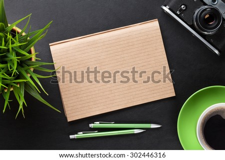 Office leather desk table with camera, supplies, coffee cup and flower. Top view with copy space - stock photo