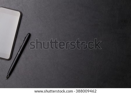 Office leather desk table with smartphone and pen. Top view with copy space - stock photo