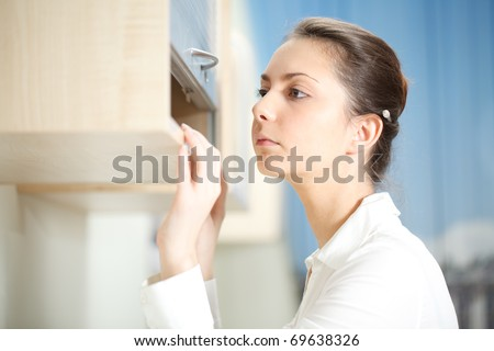 Office life. Woman searches for documents on a shelf. - stock photo