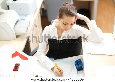 Office life. Young woman writing something at paper - stock photo