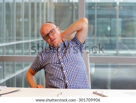 Office male worker suffering from painful tense neck muscles - stock photo
