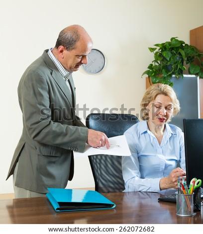 Office manager scolding elderly female secretary for mistake - stock photo