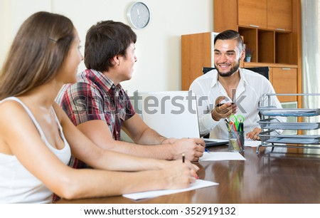 Office manager with young couple signing business paper in the office - stock photo
