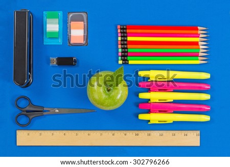 Office or back to school supplies consisting of a green apple, highlight markers, stapler, thumb drive, ruler, scissors, tab markers and colorful pencils on blue background.   - stock photo