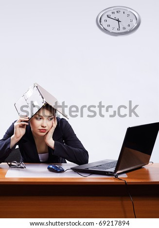 office portrait of beautiful bored business woman sitting at her workplace with two laptops on gray