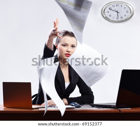 office portrait of beautiful dissatisfied business woman with two laptops angrily throwing documents to the camera - stock photo