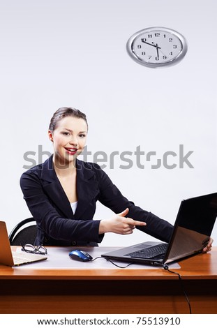 office portrait of beautiful friendly business woman sitting at her workplace and pointing on laptop - stock photo
