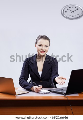 office portrait of beautiful friendly young business woman sitting at her workplace with two laptops and inviting to have a seat - stock photo