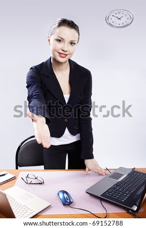 office portrait of beautiful happy business woman standing from her deck and stretching her hand for handshake at her workplace with two laptops on gray - stock photo