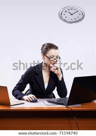 office portrait of beautiful happy young business woman in glasses sitting at her workplace with two laptops and on gray - stock photo