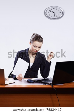 office portrait of beautiful serious concetrated business woman at her workplace with documents and two laptops on gray - stock photo