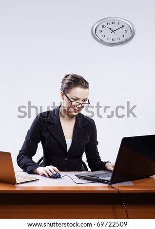 office portrait of beautiful young business woman in glasses sitting at her workplace with two laptops and block note on gray - stock photo