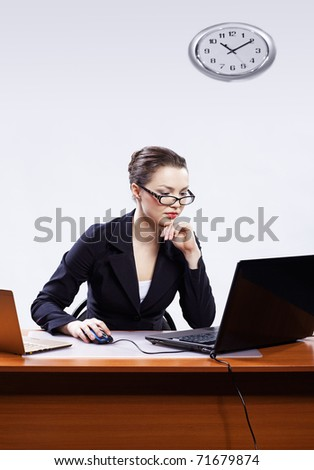 office portrait of beautiful young business woman in glasses sitting at her workplace with two laptops on gray - stock photo