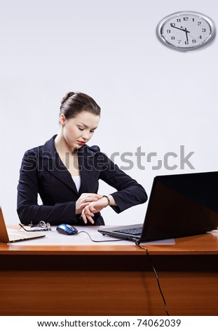 office portrait of beautiful young business woman sitting at her workplace with two laptops on gray and regulating her watches - stock photo
