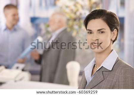 Office portrait of mid adult businesswoman looking at camera, smiling, coworkers in background.?