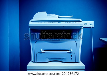 Office printer multi-functional device on table plugged in a communication port on a wall - stock photo