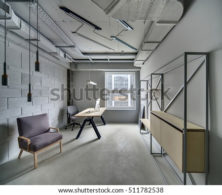Office Room In A Loft Style With Gray Walls. There Is A Wooden Table With