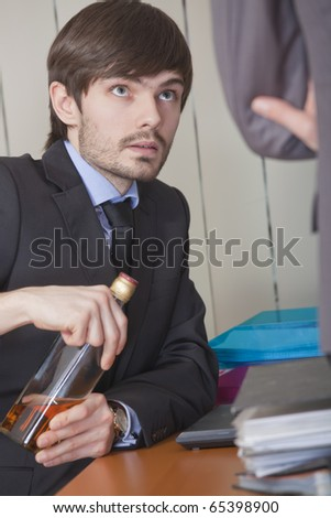 office scene - businessman hiding a bottle of alcohol under the desk