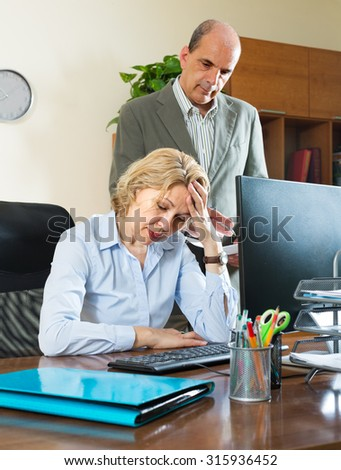 Office scene with angry chief and careless aged female secretary - stock photo