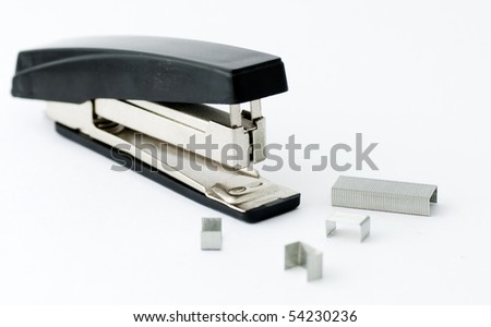 Office stapler isolated on white and some cramps near - stock photo